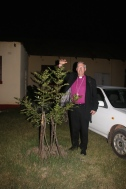 Bishop Christopher with one of the trees planted by the visitors from the Link church in Croydon
